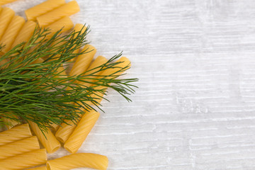 Italian pasta and dill on the wooden table