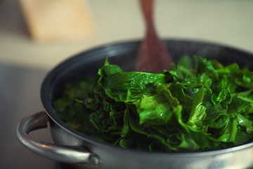 Vegetarisch voedselconcept. Verse spinazie koken in metalen pot.