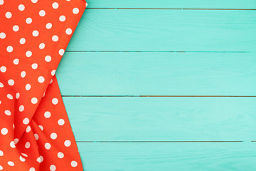 Tablecloth with polka dots on blue wooden background