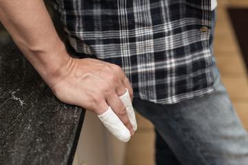 Mann lehnt mit eingegipsten Fingern an Küchenzeile