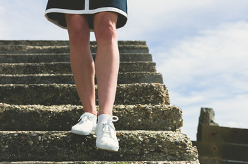 The legs of a woman walking down stairs