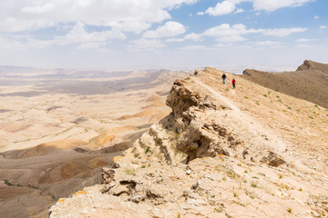 Wall Mural - Couple  walking desert mountain edge.