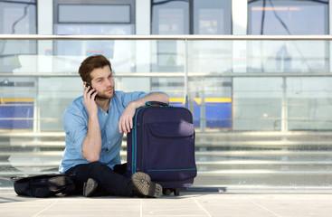 Male traveler sitting on floor talking on mobile phone