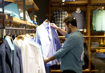 Young man shopping for clothes at store