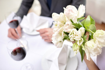 close up of couple with flowers at restaurant