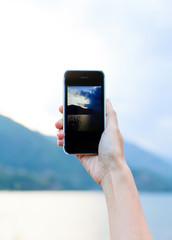 Hand taking photo of the lake landscape by smartphone