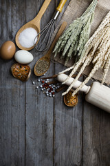 Food ingredients and kitchen utensils for cooking on wooden back
