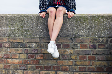 Young woman sitting on a brick wall