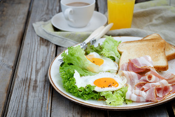 Breakfast on a plate: fried eggs, bacon and lettuce