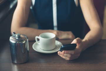 Woman having coffee and using smartphone
