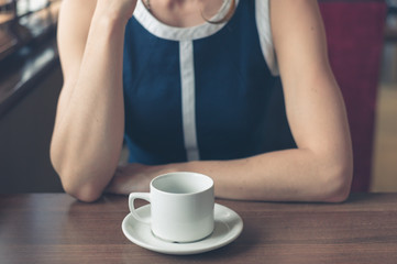 Young woman having coffee in diner