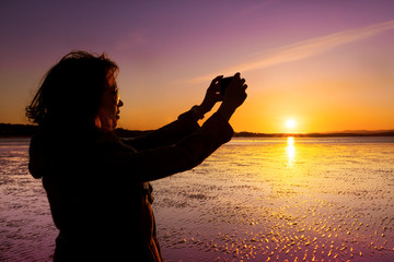 Woman taking selfie on a beach during sunset.