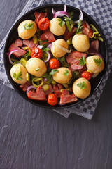 Potatoes with fried bacon and tomatoes top view vertical
