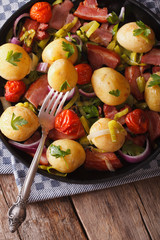 New potatoes with onions and bacon on a plate. Vertical, rustic