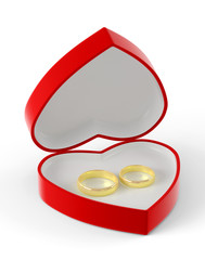 Two wedding rings lying in a red heart-shaped box