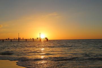 Leute im Sonnenuntergang auf dem Steg am Meer