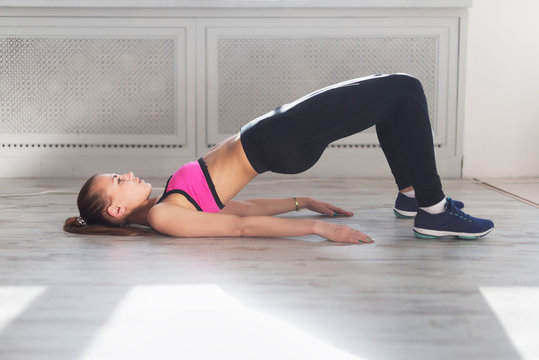 Side view of young woman doing gymnastics the half bridge pose