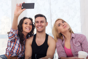 Happy friends two women and man taking selfie with camera or