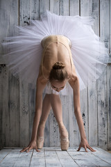 Ballerina dressed in white tutu makes lean forward