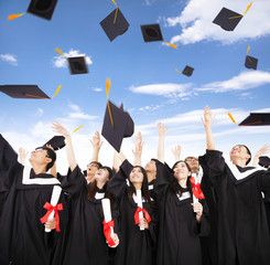 happy students throwing graduation caps into the Air