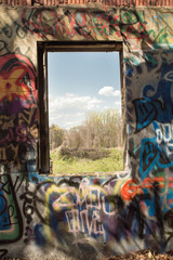 Graffiti covered wall and window to landscape