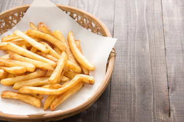 Traditional french fries in basket on wooden background.