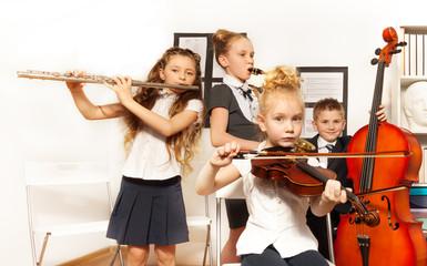 School children play musical instruments together