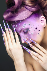 Girl with creative makeup  and long nails.