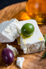 Feta cheese on wooden board with olives and oil