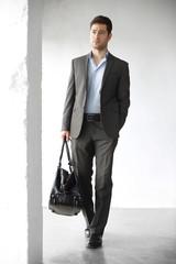 Fototapeta Podróż biznesowa. Przystojny mężczyzna w garniturze z walizką  obraz