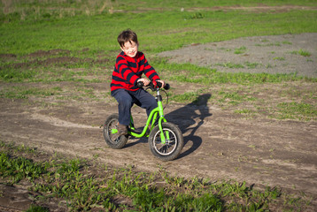 little boy rides a bicycle