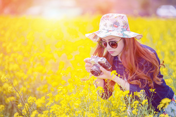 woman taking photos at a rapeseed flowers