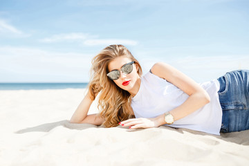 Attractive girl in sunglasses posing lying on the sea beach