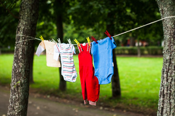 Сolorful children's clothes dry on a clothesline in the garden