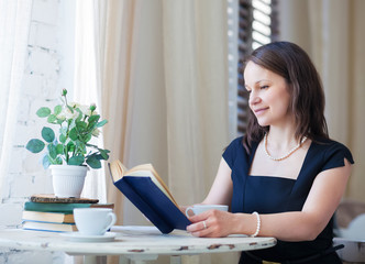 Young woman reading the book and drinking coffee