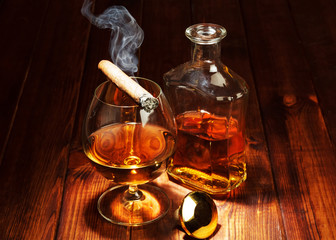 Whisky in glasses and smoking cigar