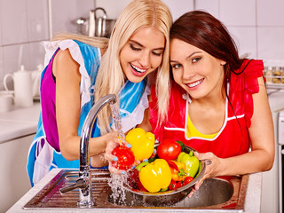 Women washing fruit at kitchen.