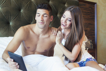 Man showing girlfriend pictures on tablet