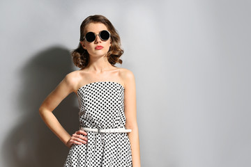Portrait of beautiful model in dots dress in sunglasses on gray background