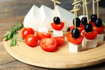 Cheese canapes with cherry tomatoes and olives on wooden tray close up