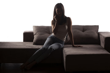 silhouette of young woman in jeans posing on the couch