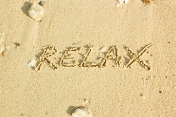 relax word handwritten on sand
