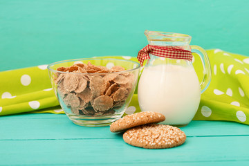 Jug of milk with muesli and cookies on blue wooden kitchen. Selective focus