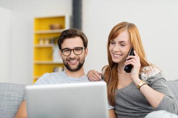glückliches paar mit laptop und telefon zu hause