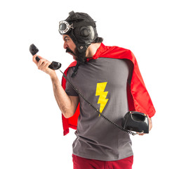 Superhero shouing by vintage phone