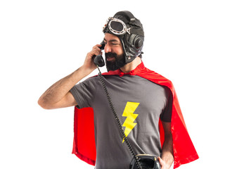 Superhero talking to vintage phone
