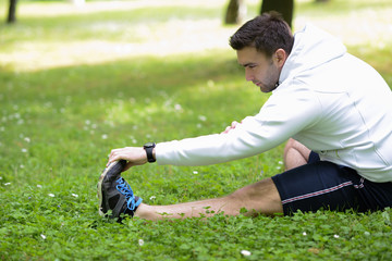 Handsome sportsman stretching outdoors