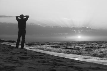 Monochrome image of man at sunrise on beach