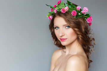 beautiful girl with wreath of flowers with bare shoulders