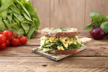 sandwich insalata verde e uova tavolo legno